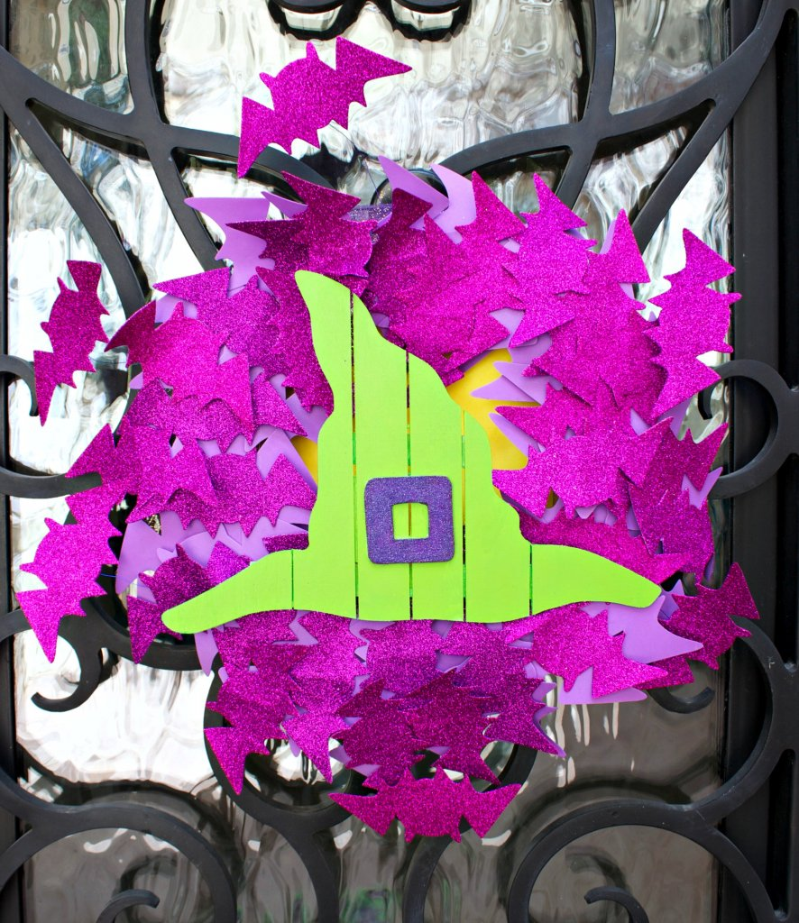 Make a bright and colorful bat wreath using items from the dollar store to create door decor that is welcoming and not too spooky.