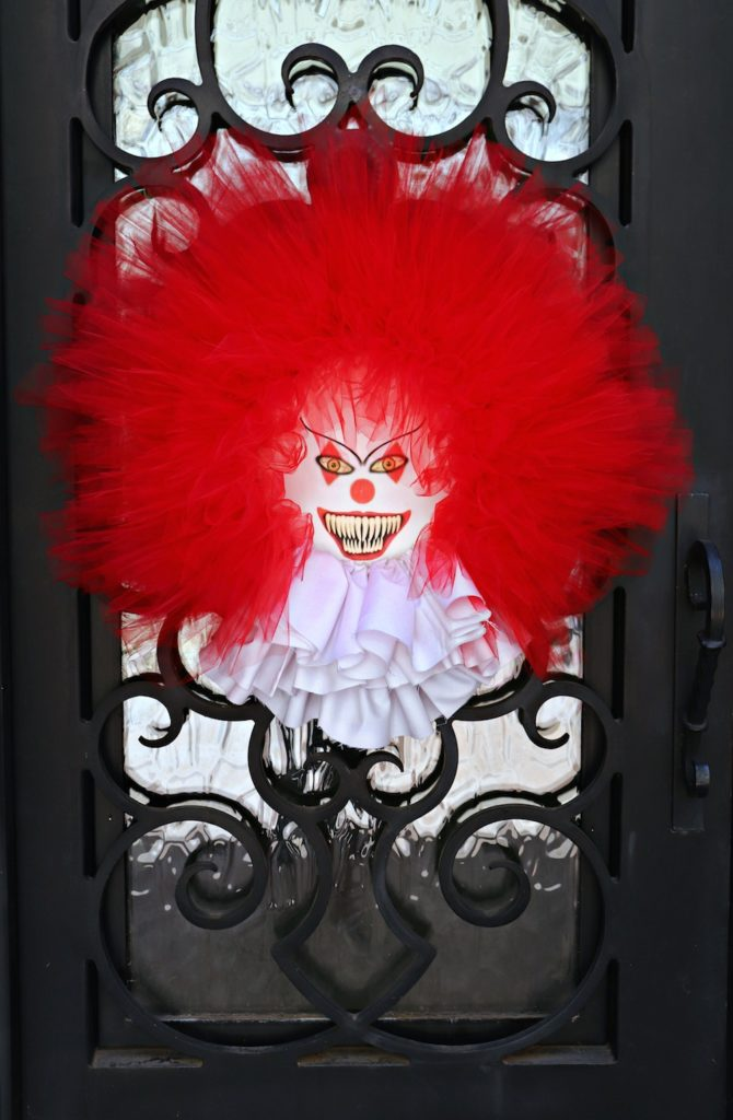 "Make a scary clown wreath that is inspired by creepy Pennywise from the hit movie and book ""It"". Tutorial includes a free printable."